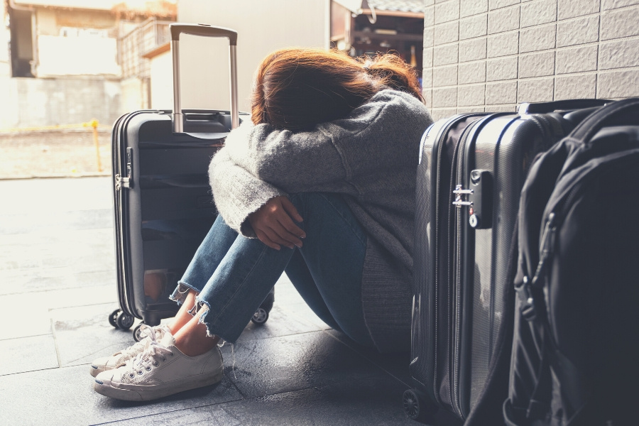 sad woman sitting with suitcases