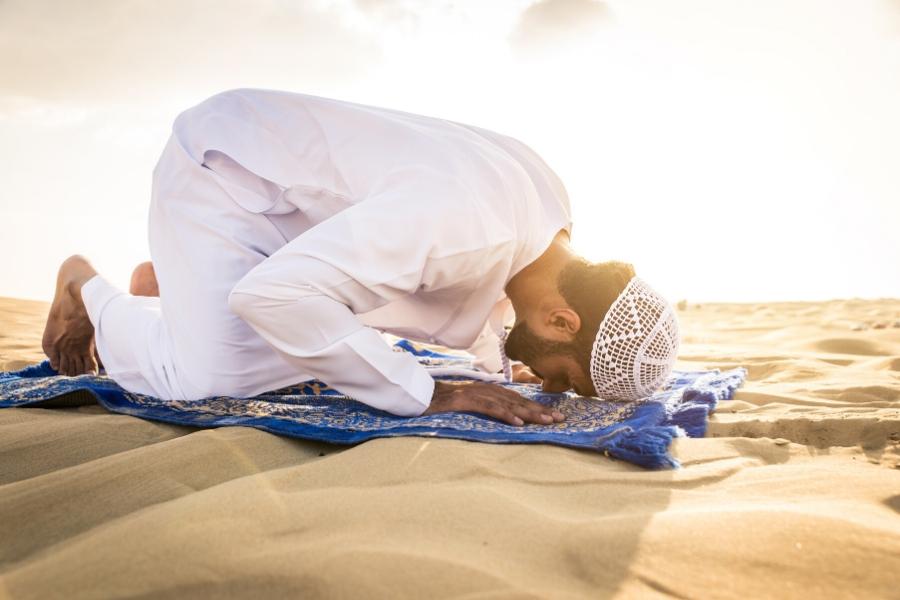 Muslim man praying in the UAE desert
