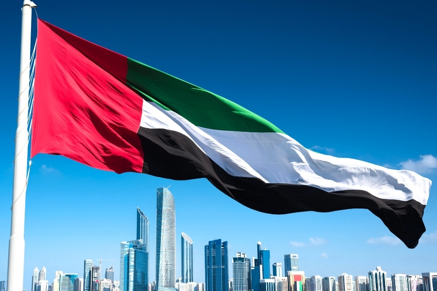 UAE flag flying above the city of Abu Dhabi skyline